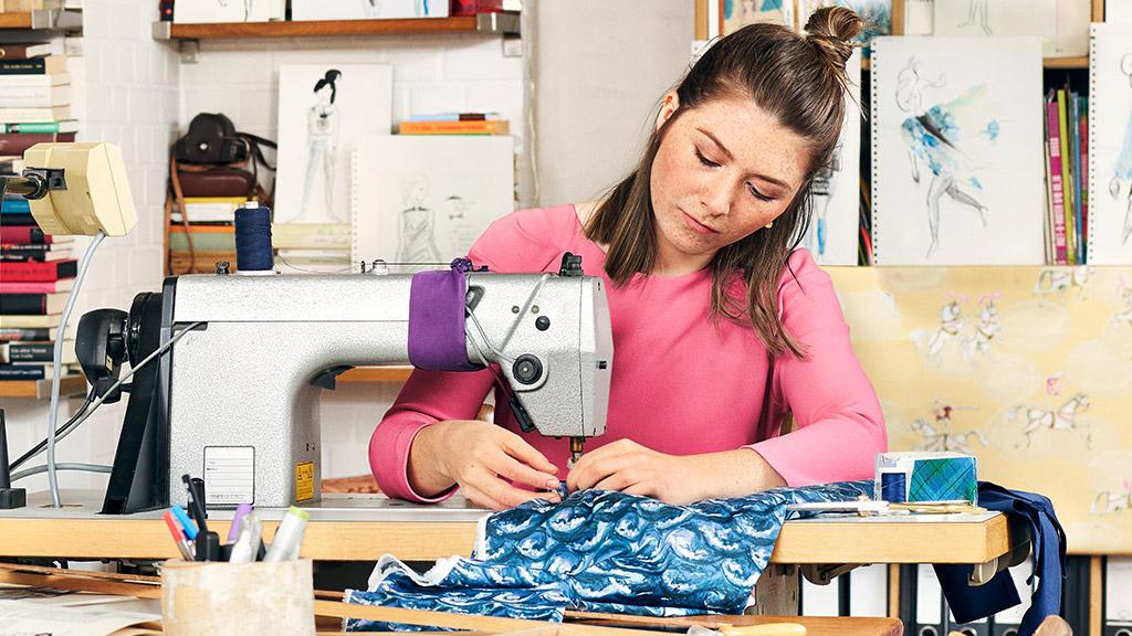 Eine junge Schneiderin sitzt in einem Atelier an der Nähmaschine.