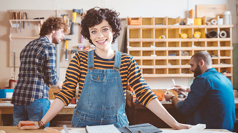 Eine junge Frau mit Latzhose steht in einer Werkstatt.