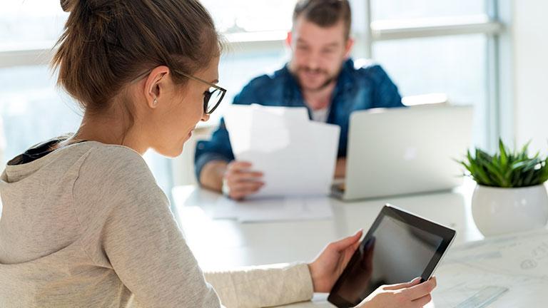 Eine Frau und im Hintergrund ein Mann lesen in Unterlagen.