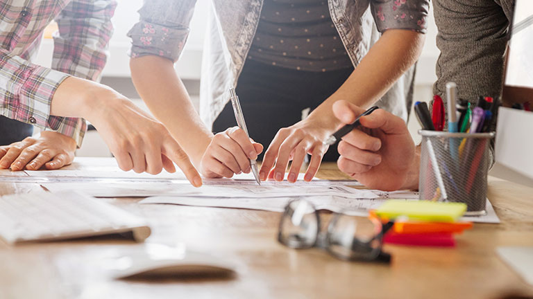 Die Hände von drei Personen zeigen auf oder schreiben auf ein Papier auf einem Tisch.