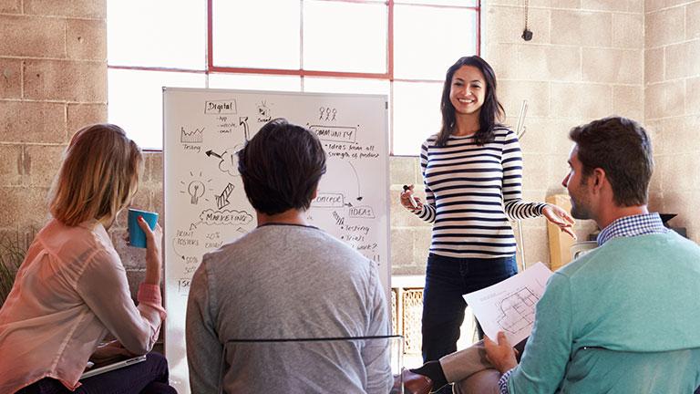 Eine junge Frau präsentiert einer Gruppe etwas an einem Whiteboard.