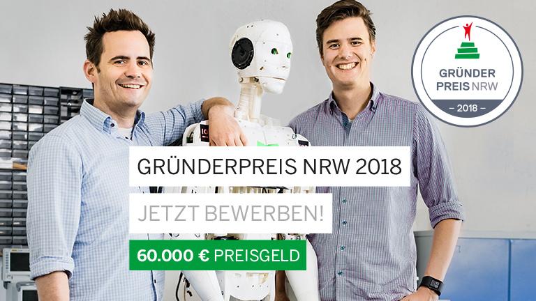 Zwei Männer posieren mit einem androiden Roboter.
