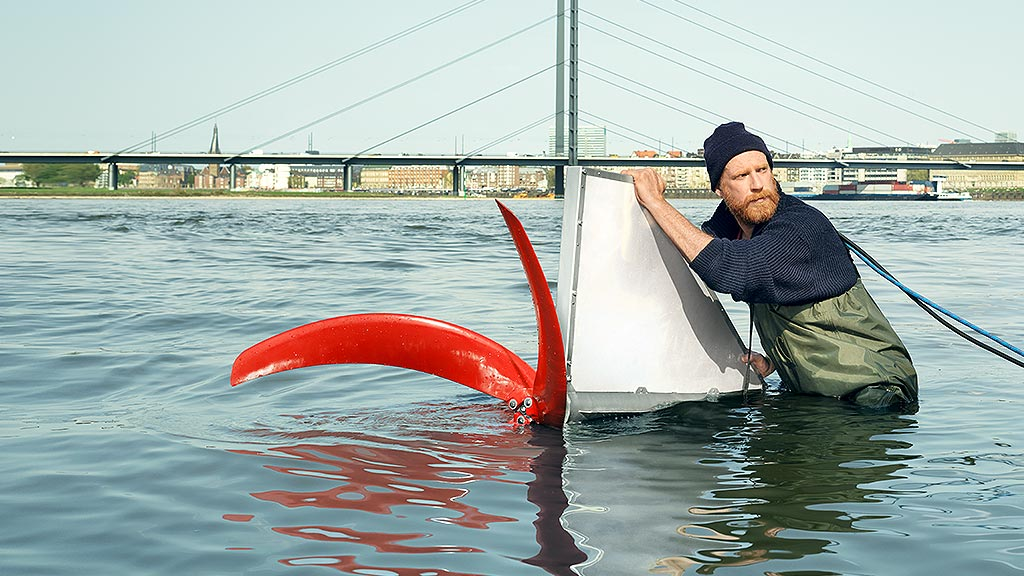 Ein Mann steht bis zur Hüfte im Wasser und schiebt eine technische Konstruktion ins Wasser.