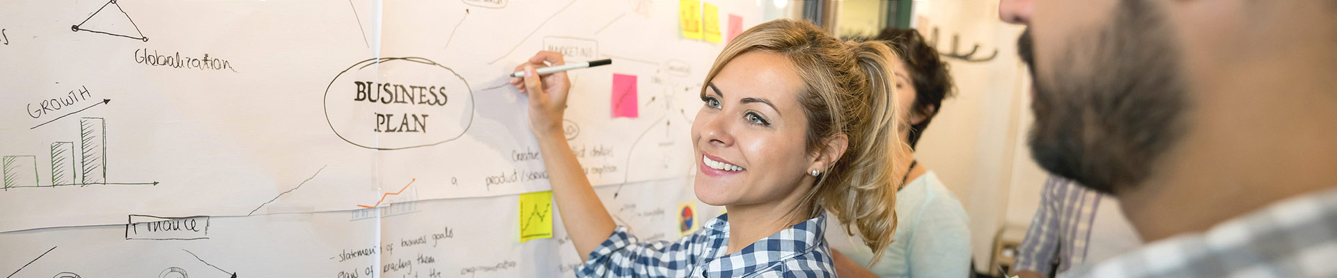 A woman creates a business plan on a metaplan wall.