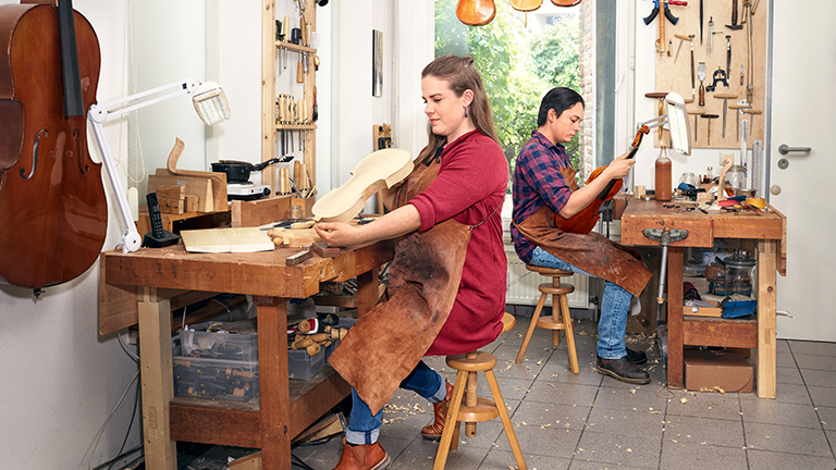 Judith Huppertz and Christoph Verstraeten in their violin making workshop, working on violins.