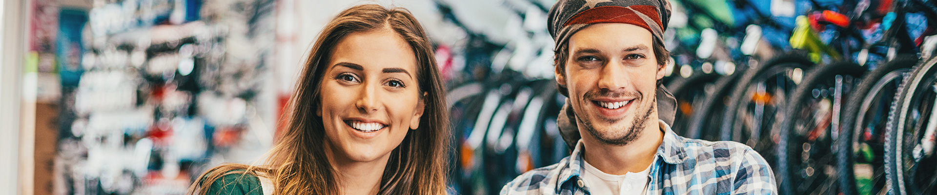 Young woman and young man in a bicycle repair shop, smiling in the camera.