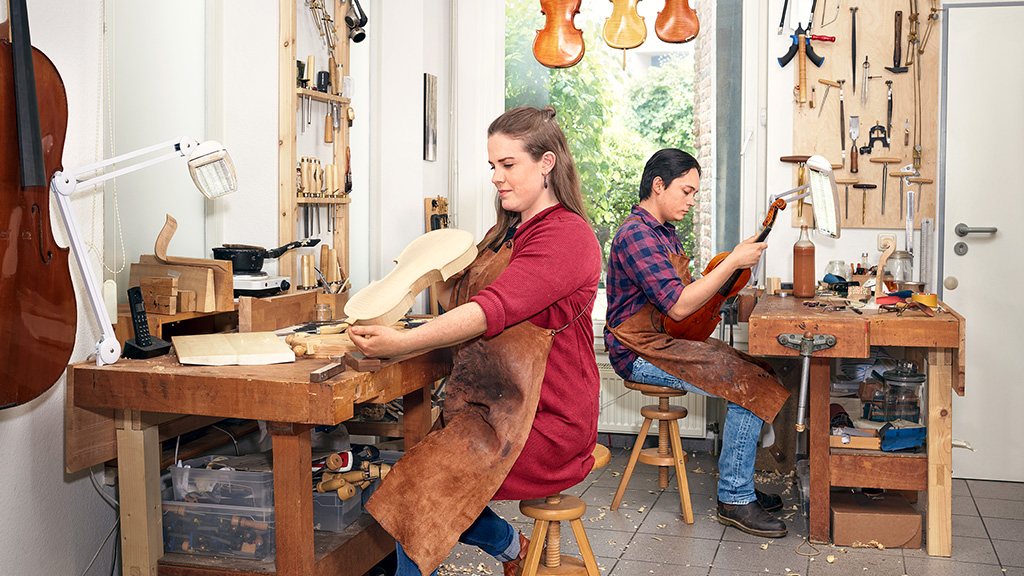 A young woman and a young man are working on violins at a repair shop.