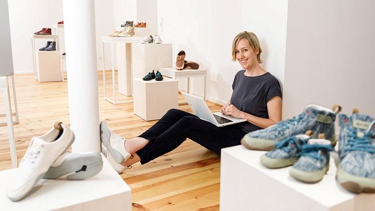 Frau sitzt mit Laptop im Schoß auf Boden, an Wand gelehnt, und lächelt in die Kamera. Um sie herum Podeste mit Sneakern