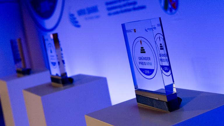 Pokale für den Gründerpreis NRW stehen auf Sockeln.