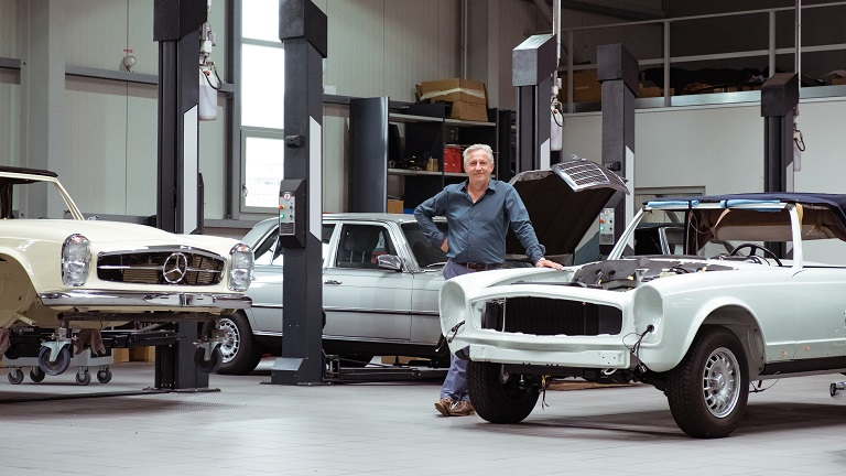 Andreas Meyer steht in der Werkstatt neben einem Auto