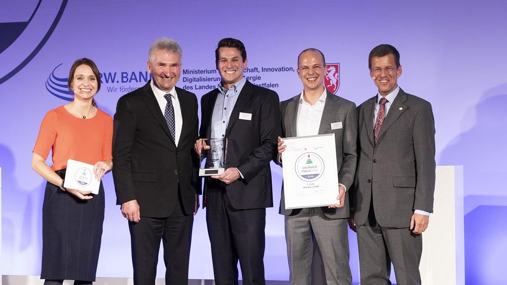 Andreas Pinkwart mit Eckhard Forst, der Moderatorin und den Gewinnern des Gründerpreis NRW 2019