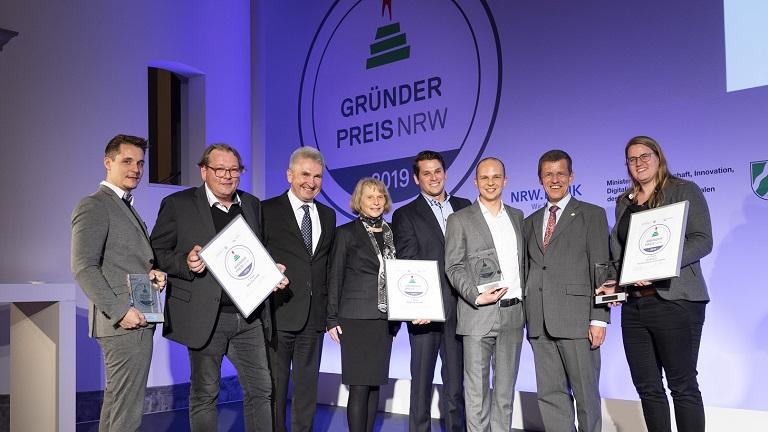 Minister Andreas Pinkwart steht mit den Gewinnern des Gründerpreises auf der Bühne