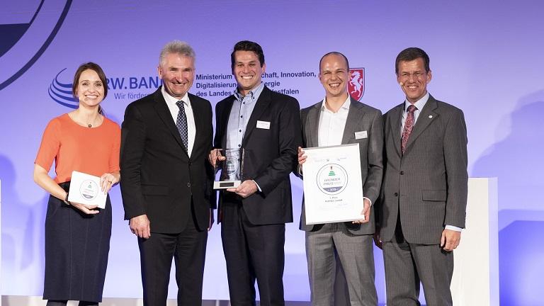 Minister Andreas Pinkwart steht mit Eckhard Forst, der Moderatorin und den Gewinnern des Gründerpreises auf der Bühne