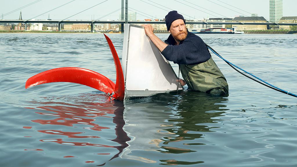 Ein Mann steht im Wasser und hält eine Konstruktion mit Schiffsschraube und Segel.
