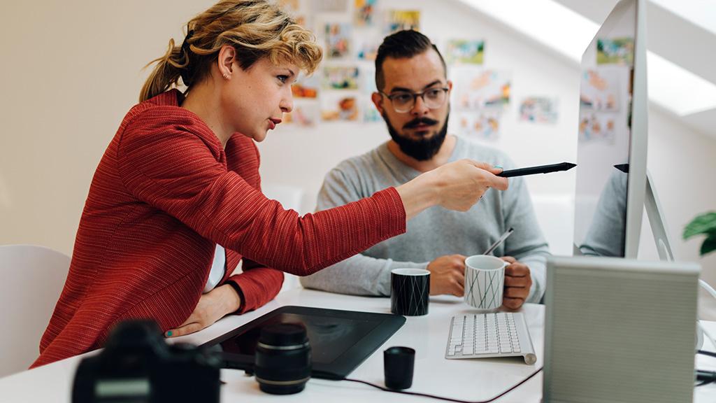 Eine Frau zeigt einem Mann etwas auf einem Computerbildschirm.