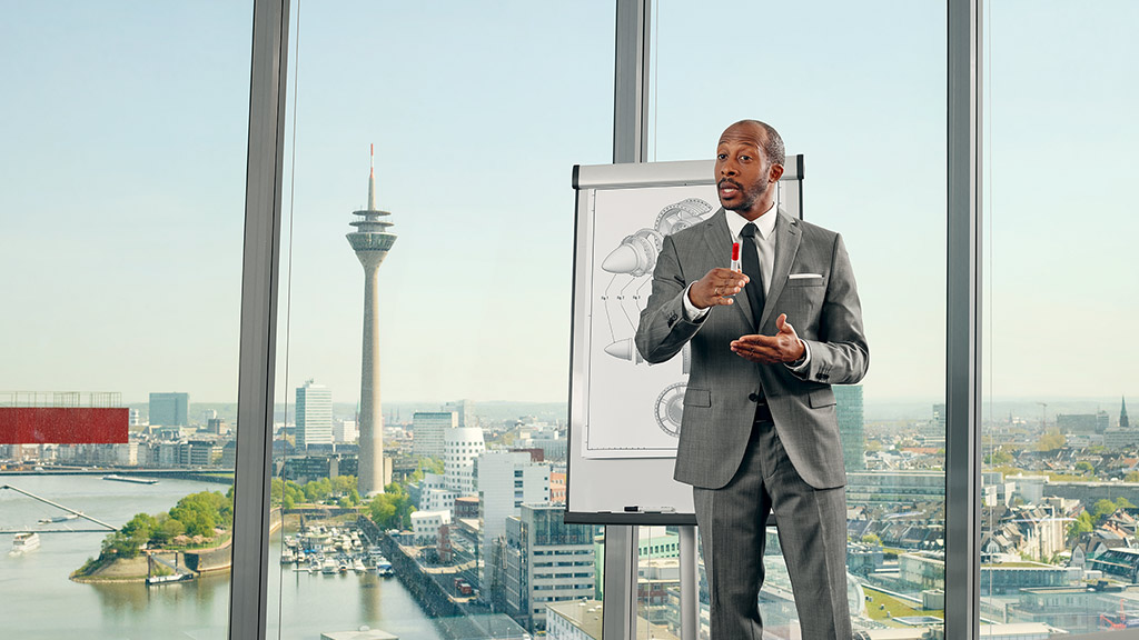 A man giving a presentation on a flipchart in front of a window with a view.