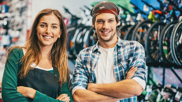 A young woman and a young man stand in the bicycle shop and smile in the camera.